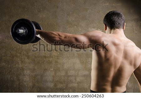 Man lifting weights, back image at old gym. - stock photo