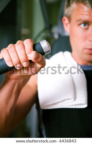 Man lifting weights in a gym, closeup on his hand - stock photo