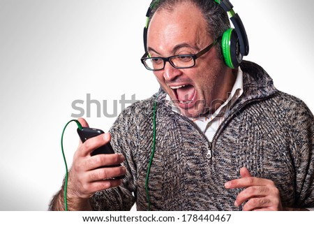 Man listen music on headphones and scream aloud. Music mobile concept - stock photo