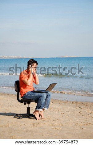 Man listening to music on the beach - stock photo