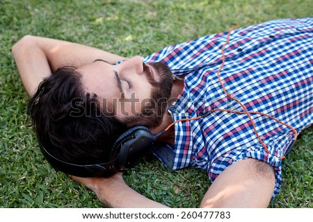 man listening to music relaxing on green grass outdoors in summer - stock photo