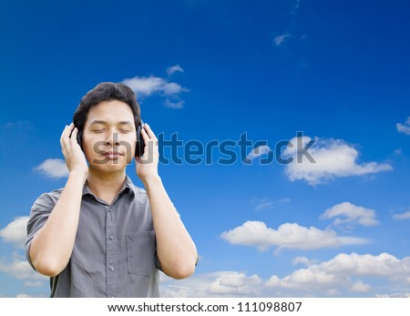 Man listening to music with headphones and blue sky - stock photo
