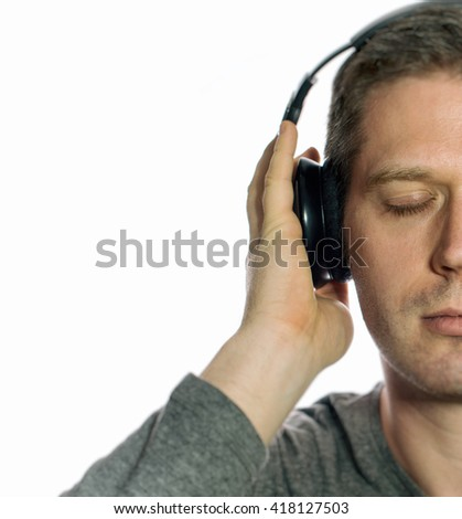 Man listening to the music in headphones. Isolated on white. - stock photo