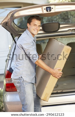 Man Loading Large Package Into Back Of Car - stock photo