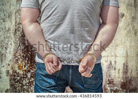 Man locked in handcuffs near wall - stock photo
