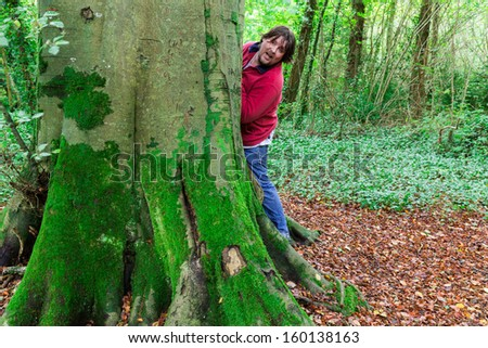 Man looking around a tree paying hide and seek in a forest - stock photo