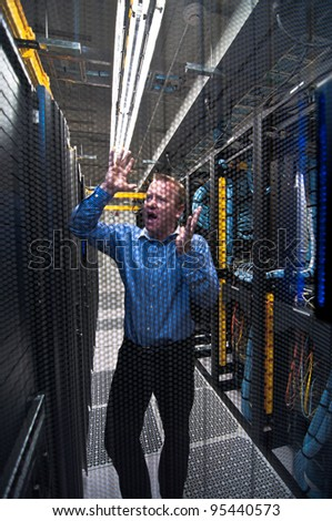 Man looking astonished in a network data center. Shot through a hexagonal door grille - stock photo