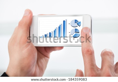 Man looking at a graph on his mobile phone as he accesses data stored in the cloud or online - stock photo