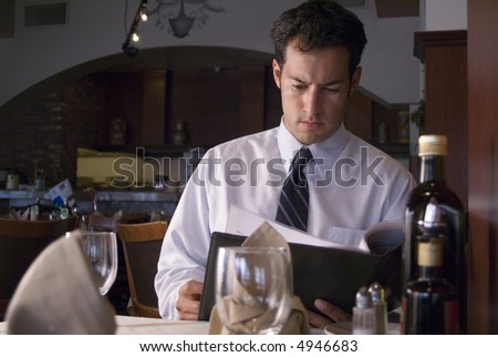 Man looking at a menu in a fancy restaurant - stock photo