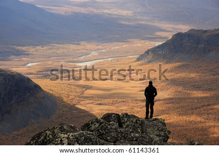 Man looking at an Arctic river valley with the colors of autumn. Sarek, Sweden - stock photo