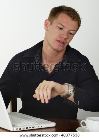 Man looking at his watch with annoyed look on he face as he works at his desk on a laptop. - stock photo