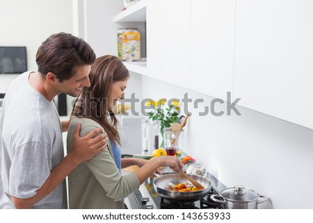 Man looking at his wife cooking in kitchen - stock photo
