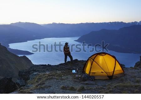 Man looking at lake by illuminated tent at dusk - stock photo