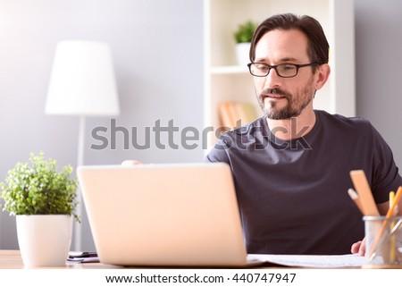 Man looking at screen of his laptop - stock photo