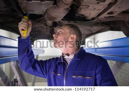 Man looking at the below of a car while repairing in a garage - stock photo