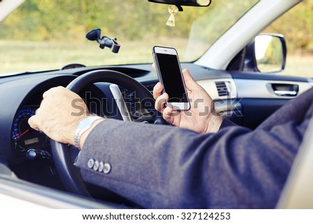 man looking at the phone while driving his car - stock photo