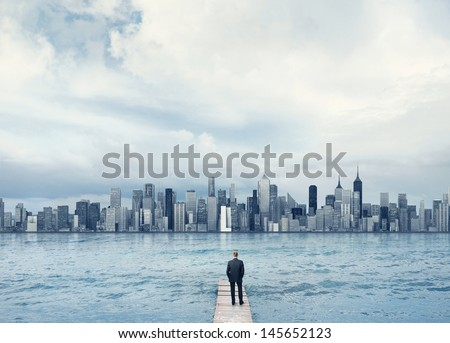 man looking at the town on a horizon - stock photo