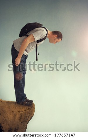 man looking down from a rocky ledge with backpack - stock photo