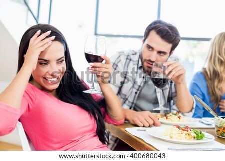 Man looking drunk woman with wine glass at home - stock photo