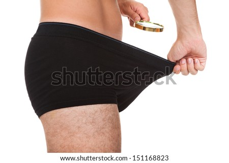 Man looking in his underwear with magnifying glass - stock photo