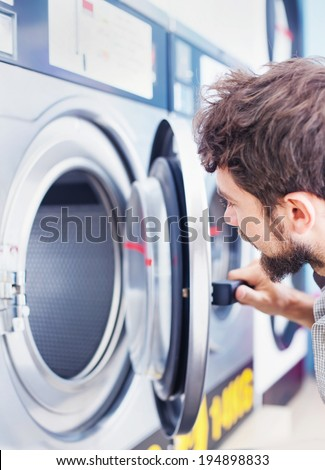 Man looking inside of the new washing machine - stock photo