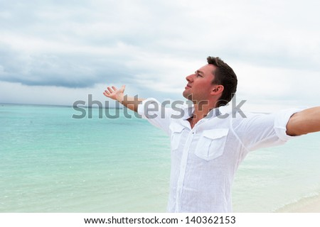 Man looking into the distance with his hands up against the sea and cloudy sky - stock photo