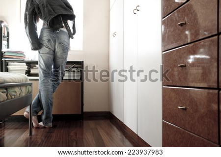 Man looking out of his bedroom window while holding a leather jacket - stock photo