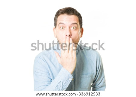 Man looking surprised covering his mouth with his hand - stock photo