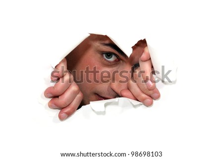 Man looking through a ripped paper wall. - stock photo