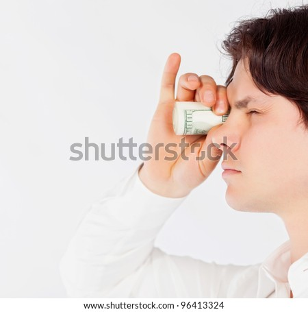 man looking through a tube of dollars - stock photo