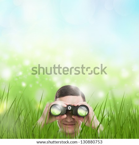 Man looking through binoculars from grass. Lots of copyspace. Head hunting or looking for something concept. - stock photo