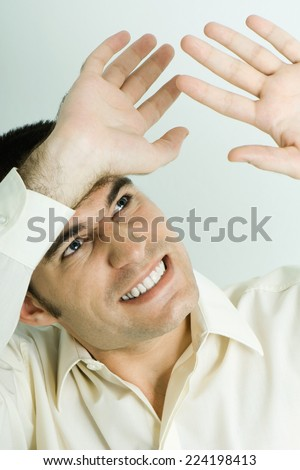 Man looking up, holding up hands protectively, head and shoulders, portrait - stock photo