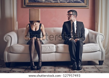 man looks at beautiful woman with box on his head sitting on the couch - stock photo