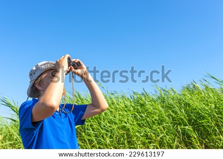 man looks for through the reeds with binoculars - stock photo