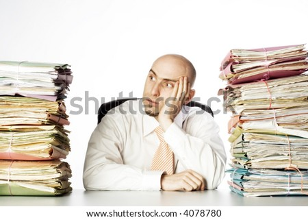 Man looks to be defeated by the piles of paperwork that flank him on either side.  Model is adult male and bald.  He has a short beard and is holding his head in one of his hands. - stock photo
