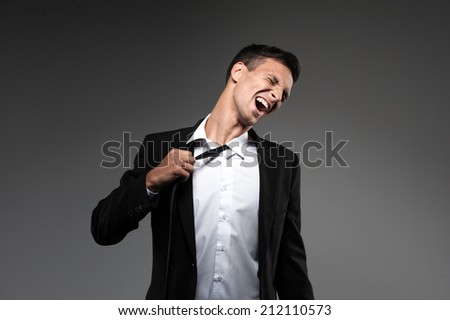 Man loosing tie on grey background. businessman in suit loosening up his tie and expressing emotions - stock photo