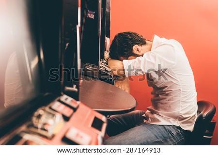 Man losing at slot machines in casino - stock photo