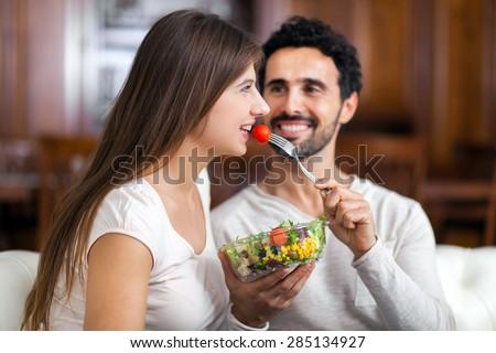 Man lovely feeding his girlfriend - stock photo