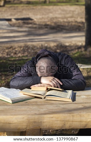 Man lying asleep on books outside on a bench - stock photo