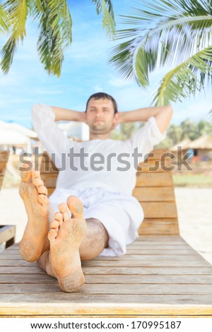 Man lying down on beach chair and relaxing in tropical resort - stock photo