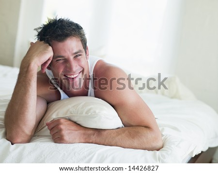 Man lying in bed smiling - stock photo