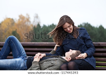 man lying in lap of young woman on park bench - stock photo