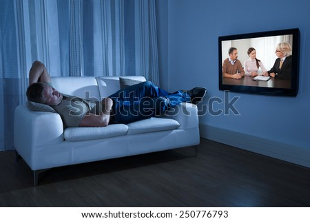 Man Lying On Couch Watching Movie At Home - stock photo