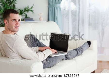 Man lying on his couch with a laptop while looking at the camera - stock photo