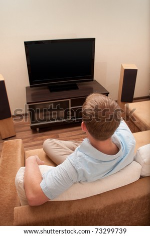 Man lying on sofa watching TV at home. - stock photo