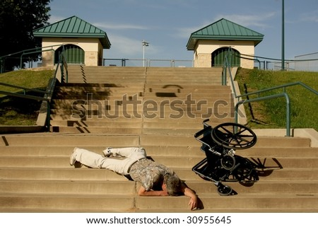 man lying on stairs after wheelchair tips over - stock photo
