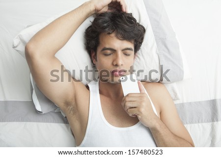 Man lying on the bed holding mobile phone  - stock photo