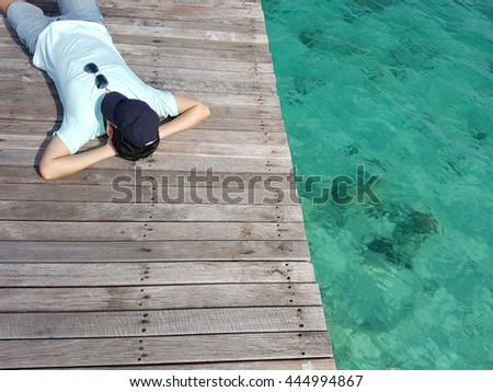Man lying on the dock pier wooden bridge with a hat and sun glass over summer sea beach for relaxation in vacation time - stock photo