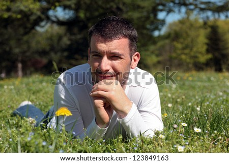 man lying on the grass in a park in spring - stock photo