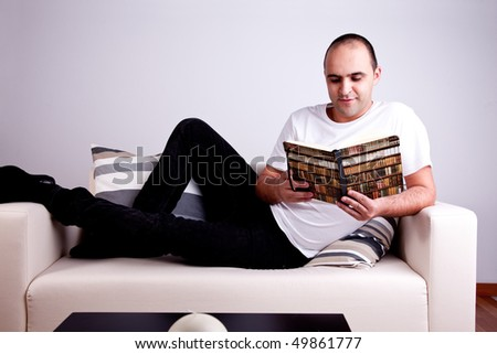 man lying on the sofa reading a book - stock photo